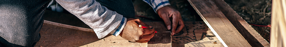 Chapter banner: Hands measuring pieces of wood at a construction site