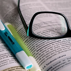 Glasses and highlighters on book page